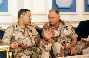The image shows Generals Colin Powell and Norman Schwarzkopf discussing things over chai.