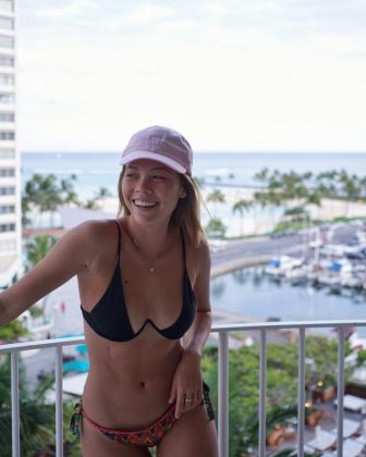 Annika Bauer laughing in a pink hat on a high-rise balcony