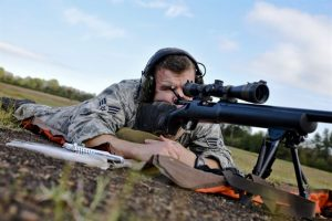 Airman looking through the scope of a sniper rifle