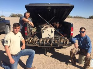 hunters posing with ducks on a truck bed.