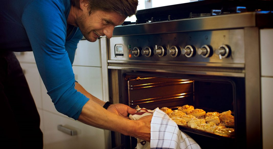 A man pulling cinnamon buns out of an oven