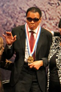 Aged Muhammad Ali waving while wearing medal around neck