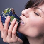 In this image a woman is devouring an cake represented to look like Earth.