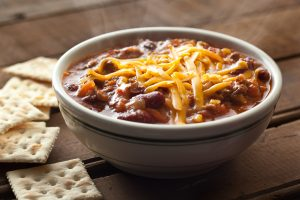 Secret Chili Recipe - Bowl of chili topped with shredded cheese and a side of crackers