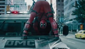 Deadpool drives a car while standing on the hood of it