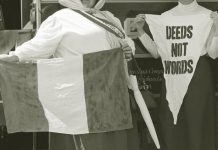 Black and white photograph macro of two suffragette holding a flag and pennant. The pennant says deeds not words.
