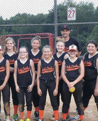 A girls' softball team poses at home plate with thier volunteer coaches for a pic.