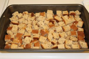 cubed bread placed on bottom pan for Baked Apple French Toast
