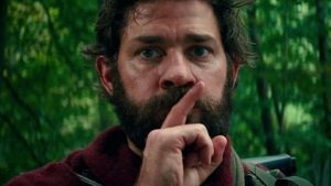 Lee Abbott (Krasinski) with his finger over his lips signaling to be quiet.