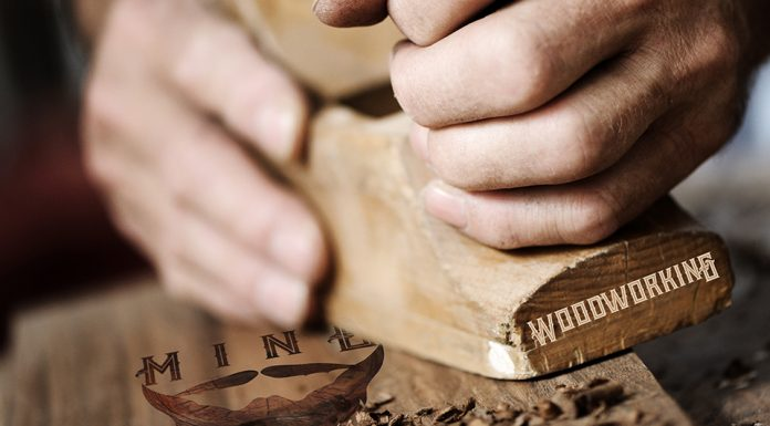 Hands of a carpenter planing a plank of wood with a hand plane.