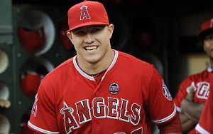 Mike Trout smiles in a dugout, though he will not be an All-Star