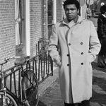 Muhammad Ali walking down the street in a tan trench coat