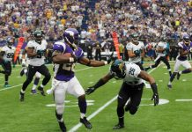 Adrian Peterson running, about to stiff arm Jaguars' #26.