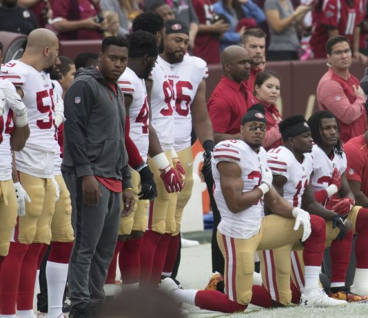 Three San Fransisco players kneeling next to rest of team