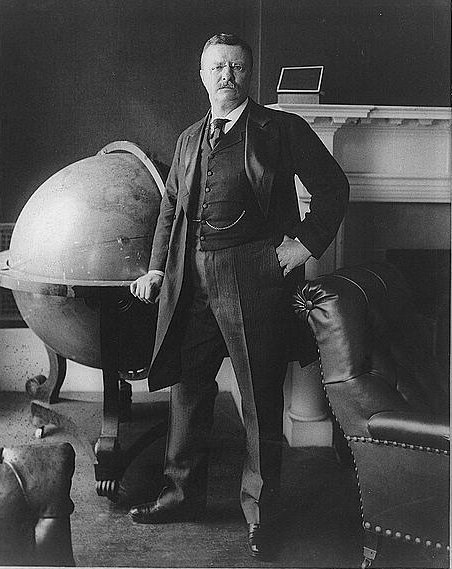 Teddy Roosevelt standing by his globe