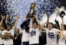 Villanova celebrates and hoist the trophy as confetti falls.