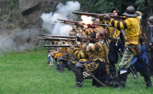 Reenactment of war with Men shooting Rifles