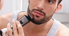 Guy using a beard trimmer for manscaping