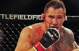 a bloody MMA fighter pulling out his mouth guard.