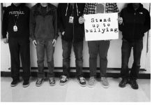 "Picture of the lower half of people while one holds a sign that says, ""Stand up to bullying."""