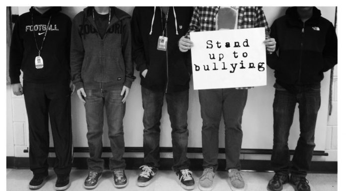 """Picture of the lower half of people while one holds a sign that says, """"Stand up to bullying."""""""