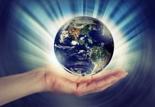 Large hand holding the Earth with a shinging light and blue background