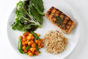 A full meal of salmon, rice, mixed carrots and green beans, and a leafy vegetable after cooking