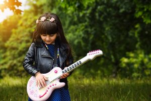 "young girl pretending to ""rock out"" on her fake guitar"