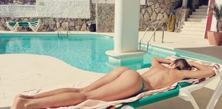 Picture of a topless woman lying down on a pool side lounger, showing her backside.