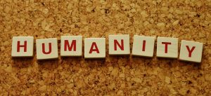 Scrabble letters arranged to spell out 'humanity'