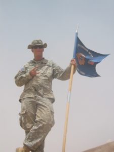 Robb Lee standing with his unit guidon