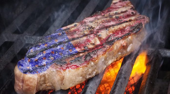 A red, white, and blue steak on a lit grill for Memorial Day
