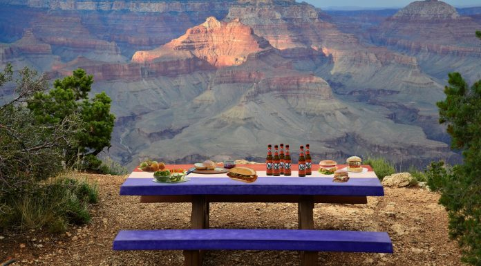 picnic table with side dishes on it