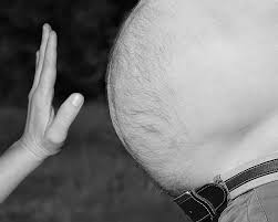 A hand held in front of a large male stomach