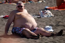 Obese man sitting on the beach. Example of poor nutrition