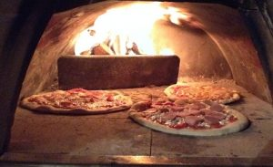 three pizzas baking in wood-burning oven