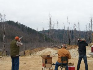 3 men shooting clay targets with shotguns before hunting season