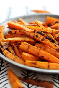 Grilled carrots sitting on a side dish after cooking