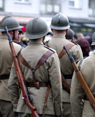 Foreign soldiers with metal helmets in beige uniforms with a rifle slung upon their backs