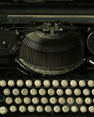 Vertical shot of an early 20th century typewriter on a wooden table