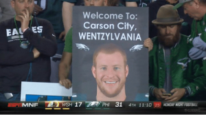 "A fan holding up a sign that says ""Welcome to Carson City, Wentzlvania"